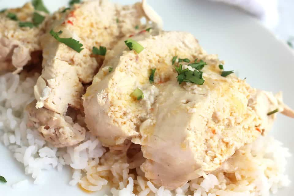 Sliced poached chiken on a bed of rice and garnished with cilantro.