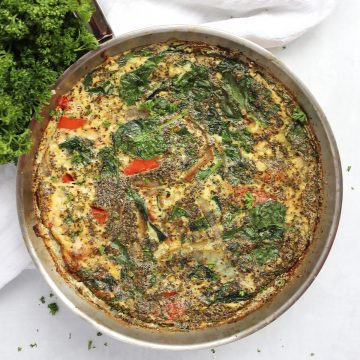 A baked egg white frittata in a skillet garnished with fresh parsley.