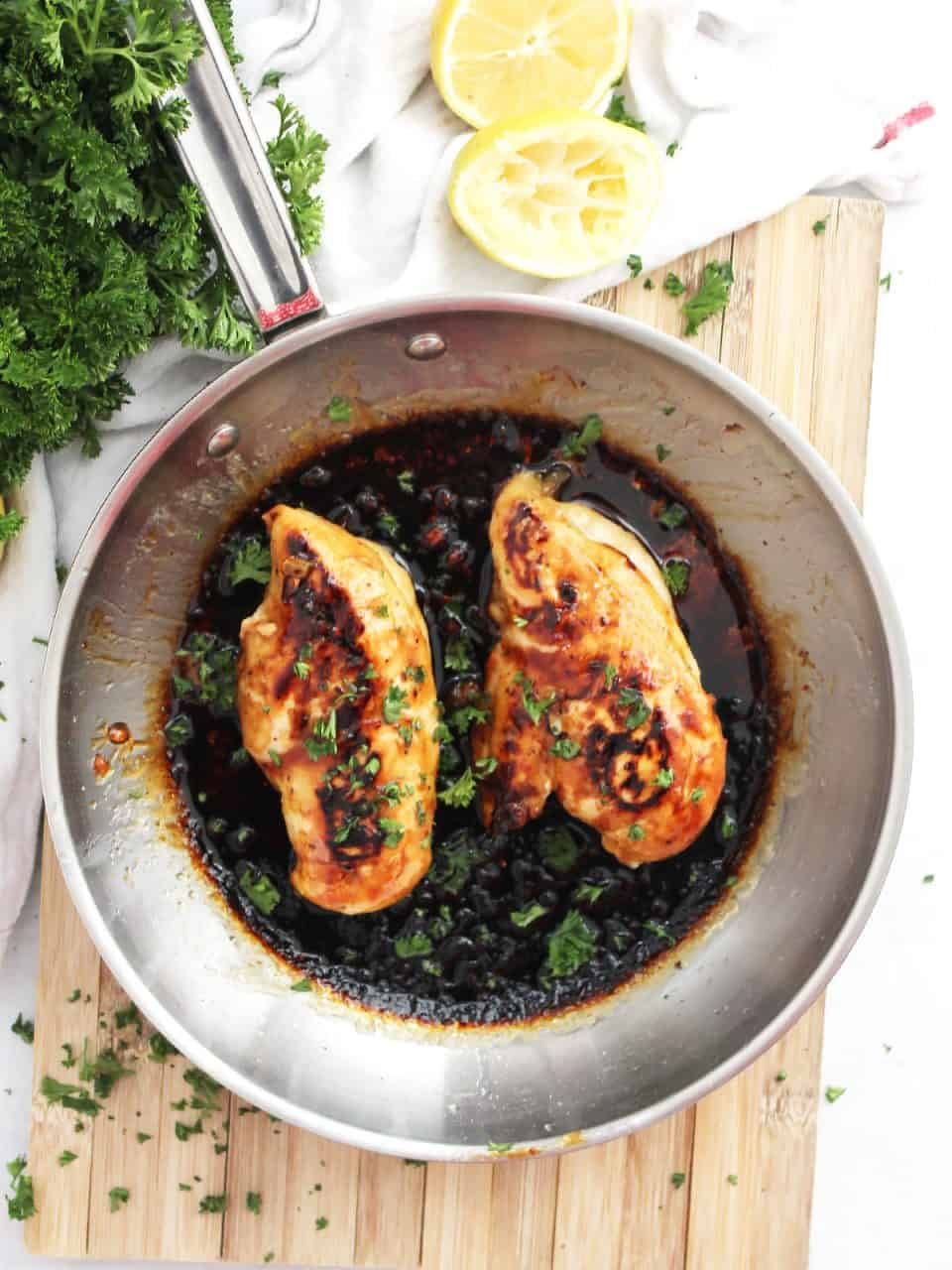 Two cooked chicken breasts in a skillet with the honey lemon sauce.