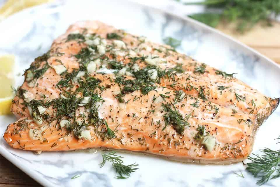 Baked honey lemon salmon fillet on a marble serving plate.