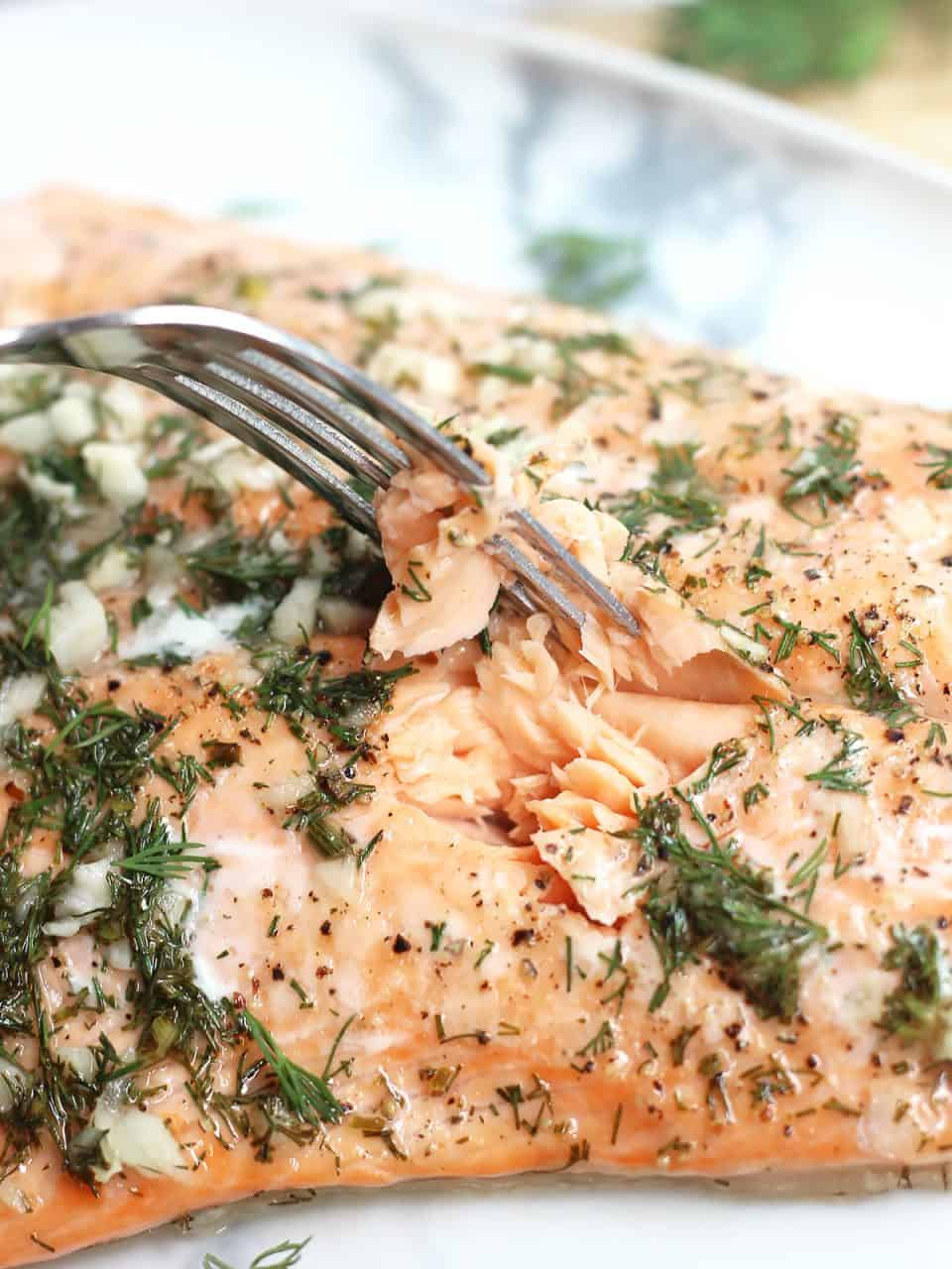 A fork flaking the flesh of the baked salmon.