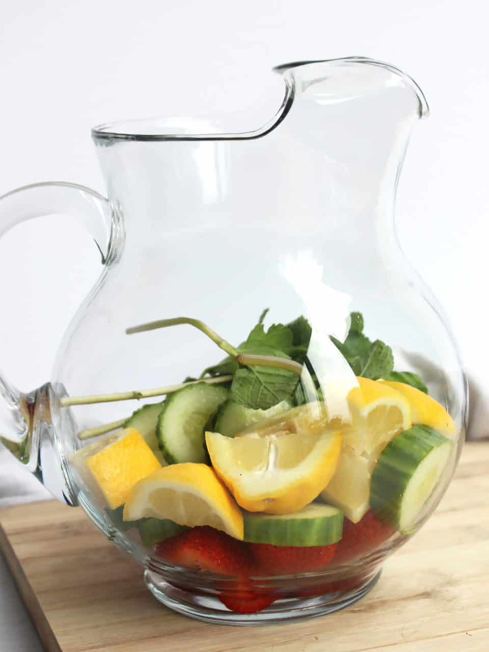 SLices of fresh fruit and mint leaves in a glass jug.