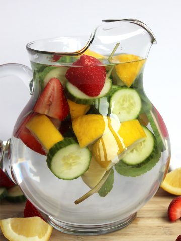 Strawberry infused water with lemon, cucumber and mint in a glass jug.