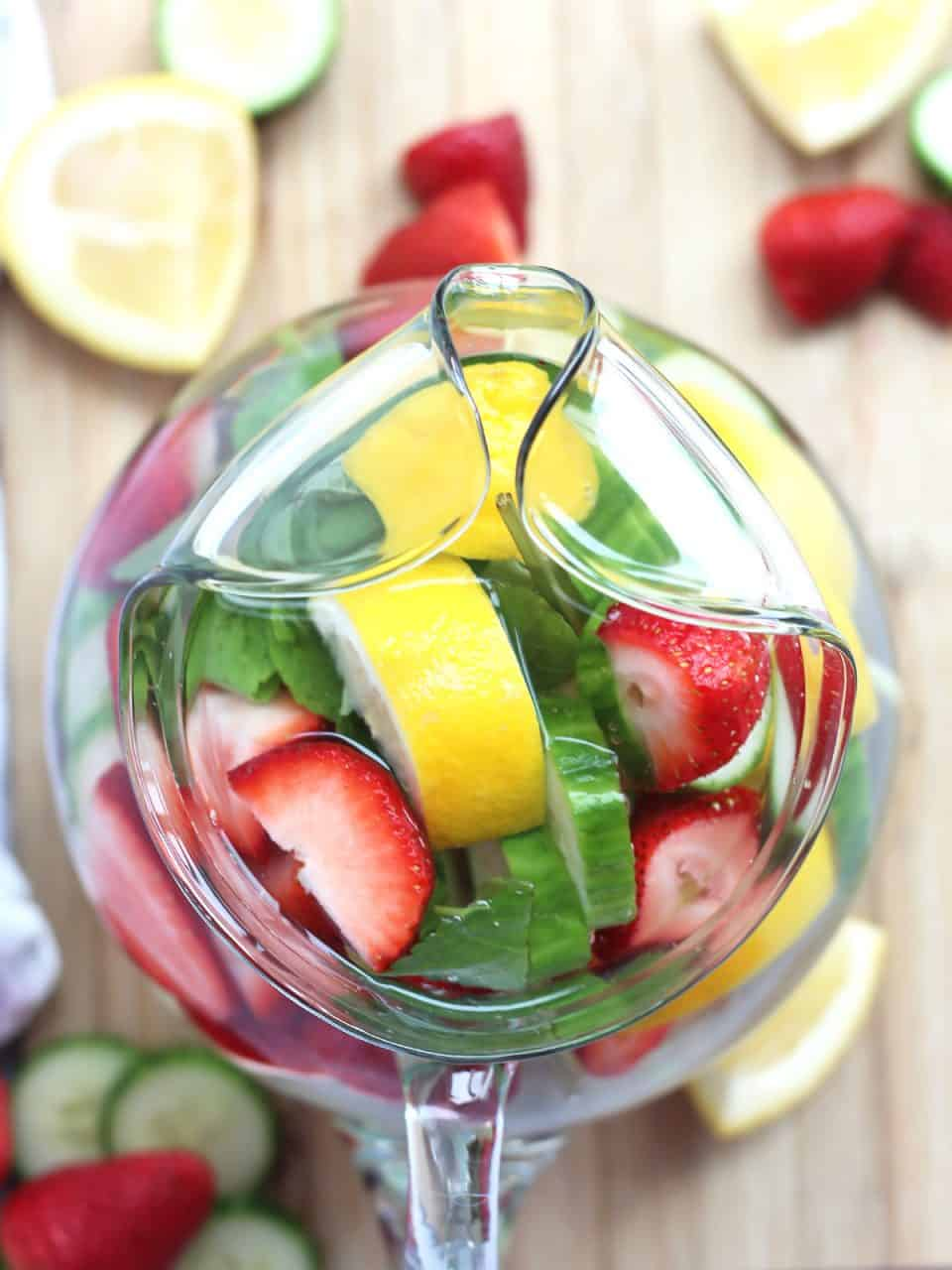 Overhead shot of the strawberry infused water in a glass jug.