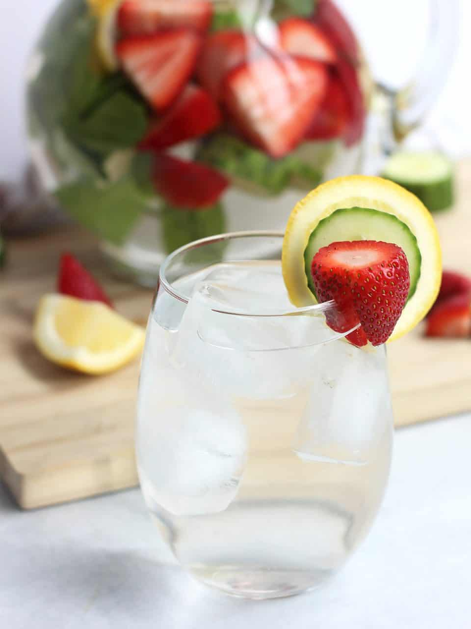 The flavored water in a glass with ice and garnished with slices of fresh fruit.