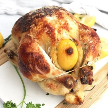 Buttermilk roasted chicken on a wooden chopping board next to fresh lemons and herbs.