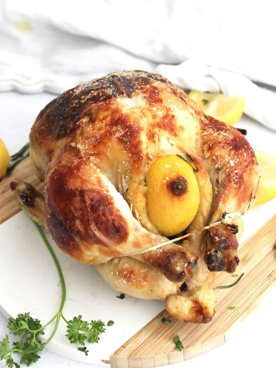 A whole roasted buttermilk chicken with legs trussed together next to fresh herbs and lemons on a chopping board.