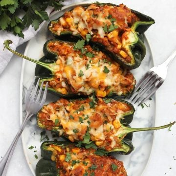 Chicken, cheese and corn stuffed poblano pepper halves on a white serving plate with two forks.