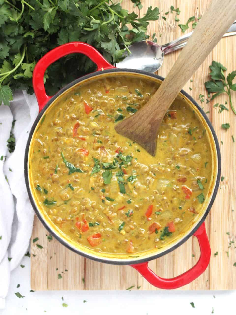 The soup in a dutch oven with a wooden spoon.