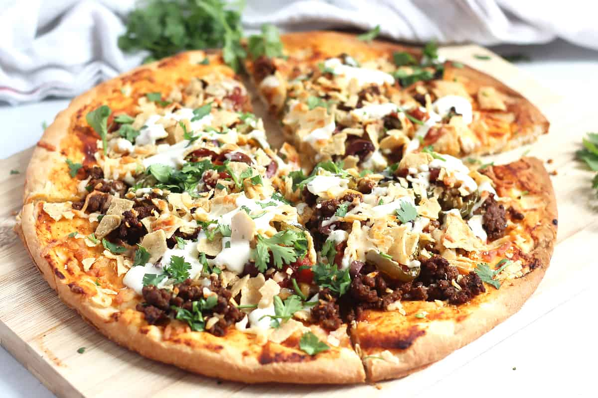 A nacho pizza topped with fresh cilantro.