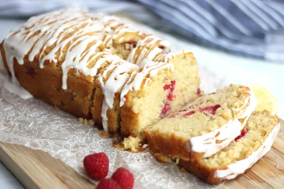Lemon and raspberry pound cake on a wooden board with two slices cut off.