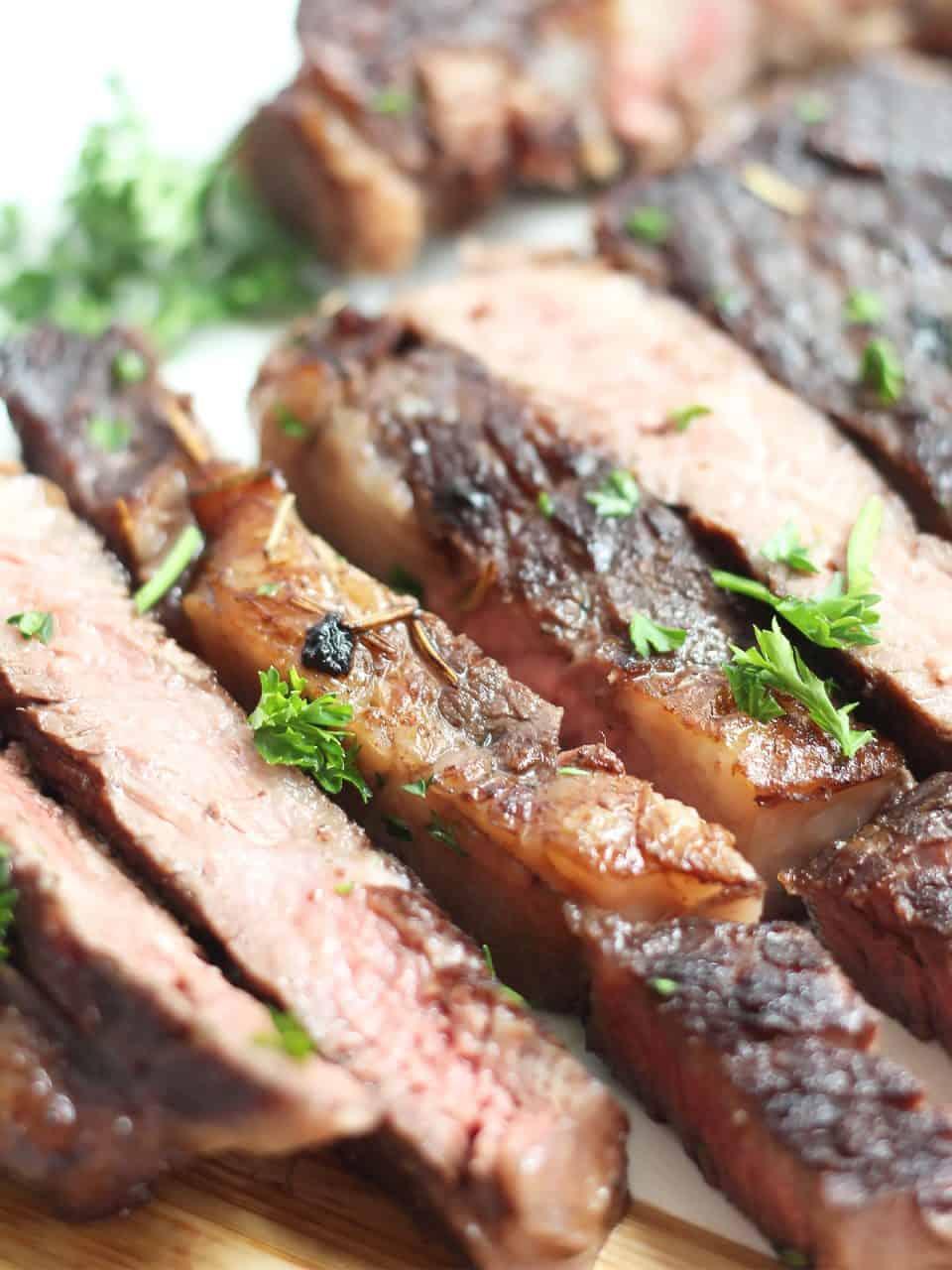 Fresh parsley sprinkled over slices of red wine marinated steak.