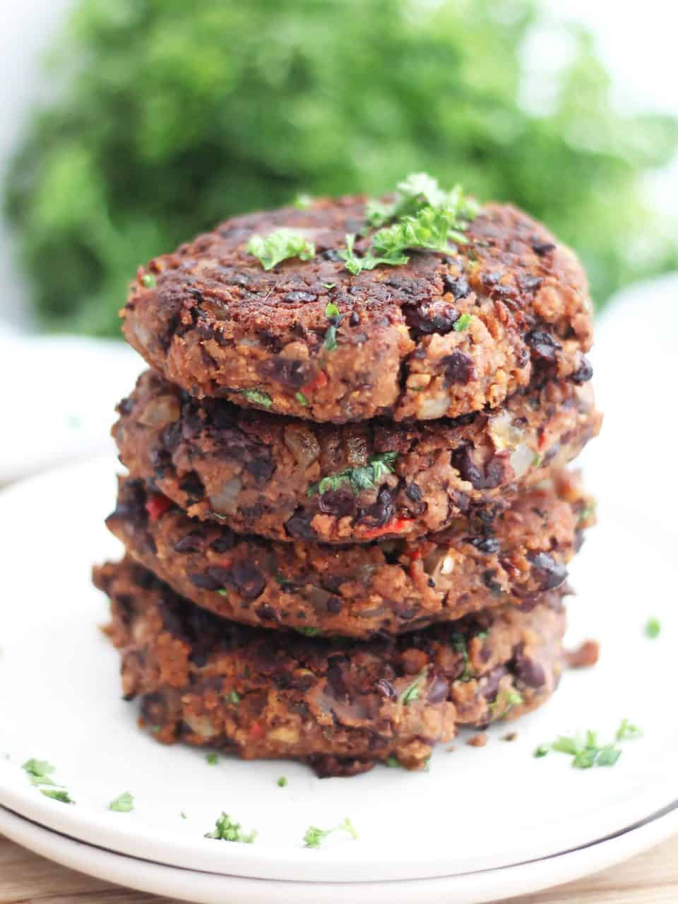 Four burger patties stacked on top of each other with parsley garnish.