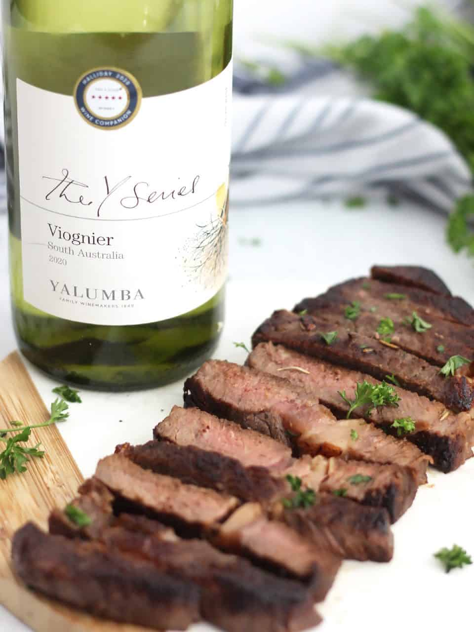 Slices of marinated steak on a chopping board in front of a bottle of white wine.