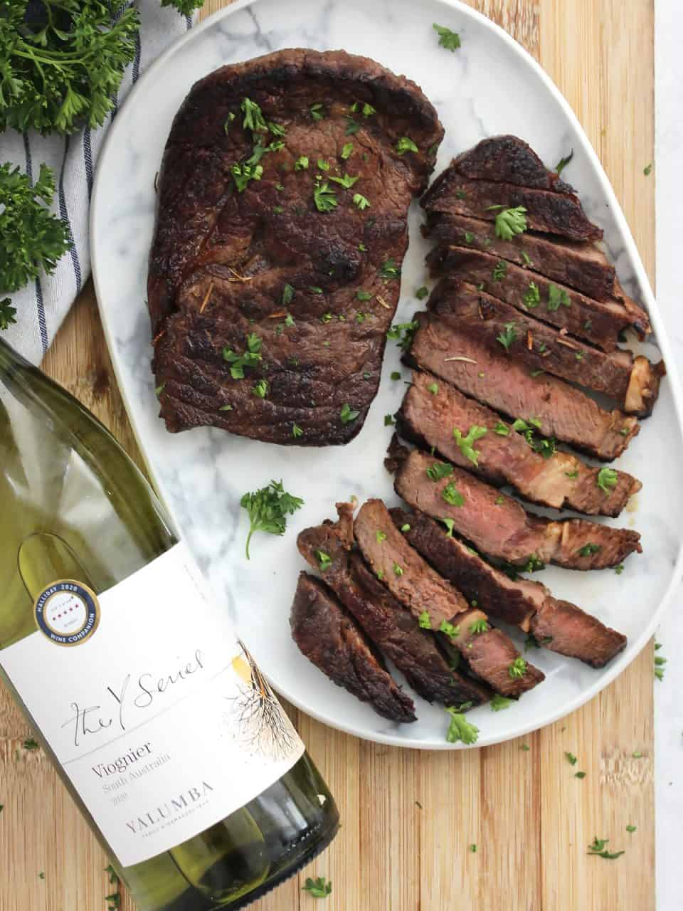 Sliced ribeye steak on a white serving plate next to a bottle of wine.