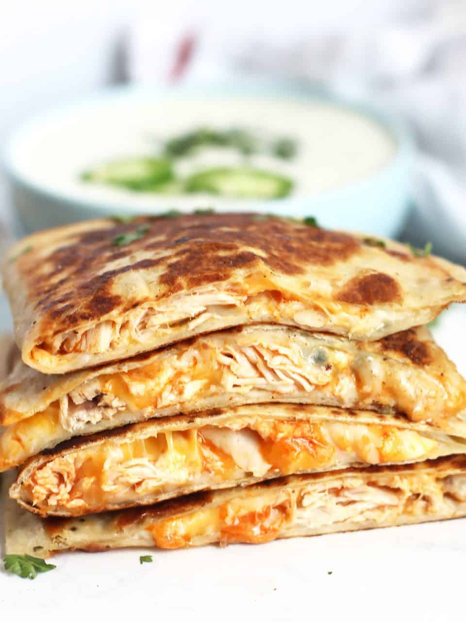 Buffalo chicken quesadillas stacked on top of each other in front of a bowl of sour cream dip.