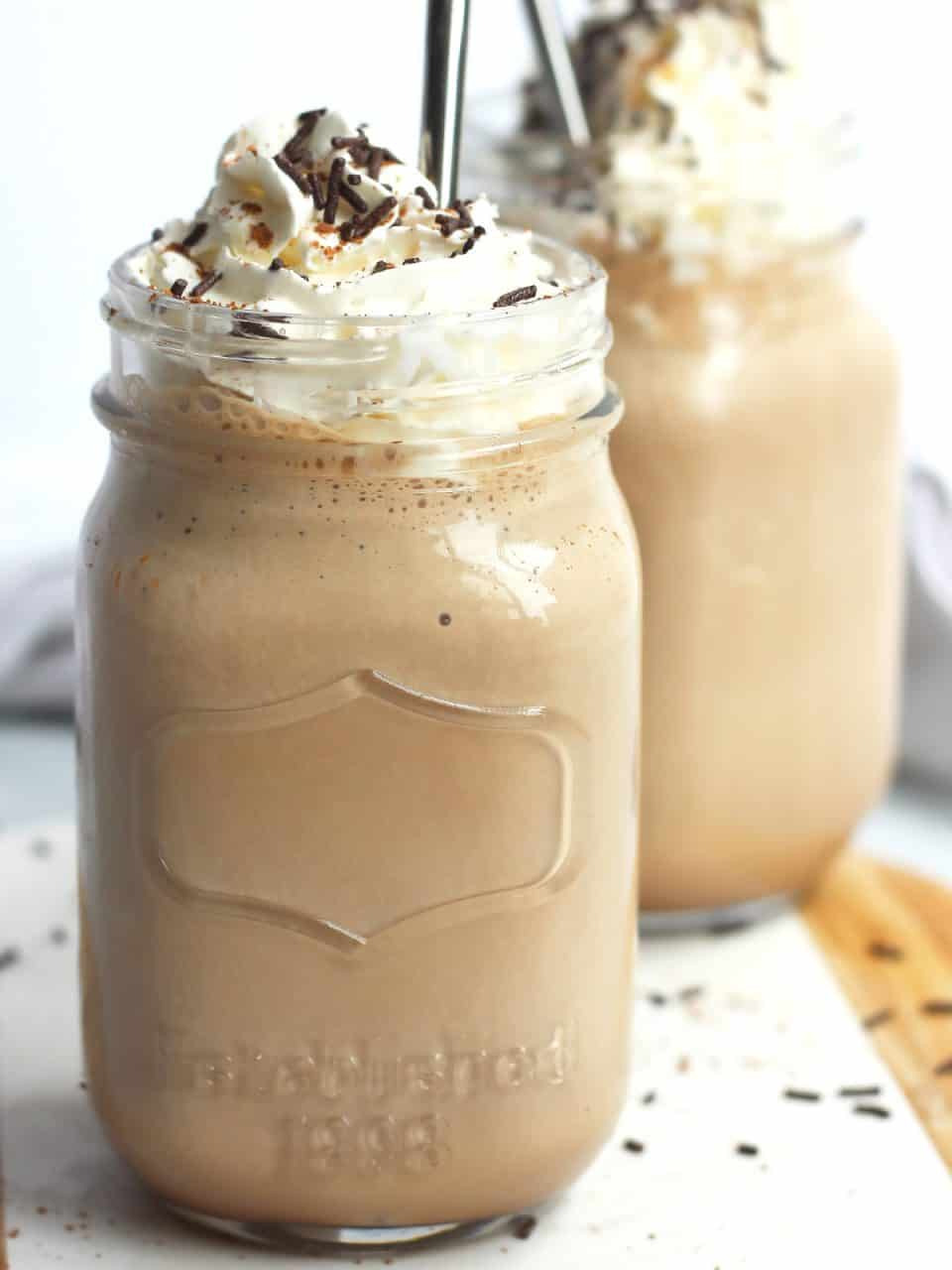 Two mason jars filled with chocolate coffee milkshake and topped with whipped cream.