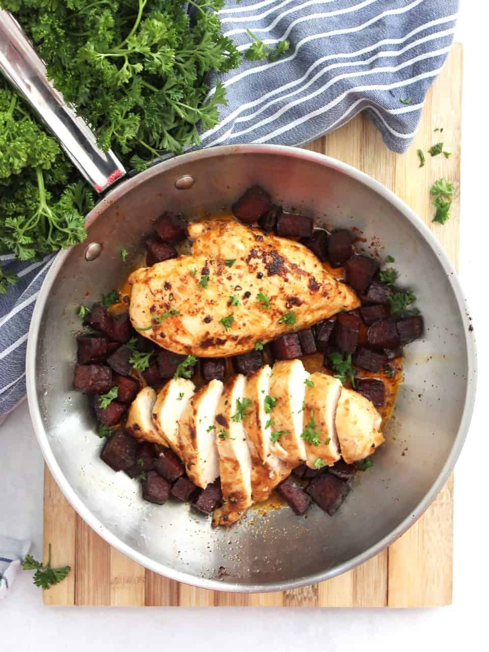 Two chicken breasts in a skillet with chorizo. One chicken breast is sliced into pieces.