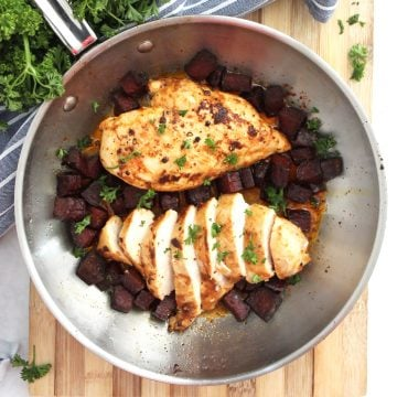 Two chicken breasts in a skillet with chorizo pieces.