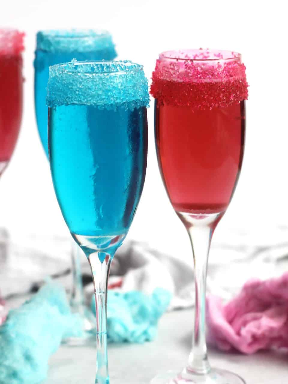 A blue and pink cotton candy champagne cocktail in flute glasses with colored sugared rims.