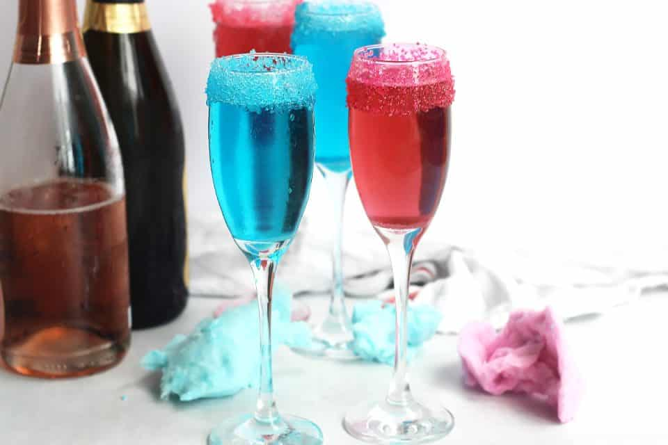 Cotton candy champagne cocktails next to two champagne bottles.