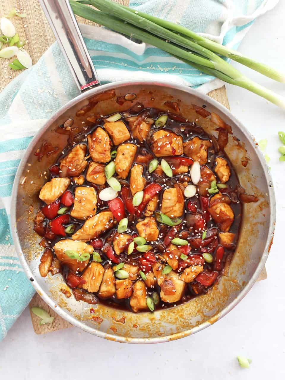 Honey sriracha chicken in a silver skillet, garnished with green onions and sesame seeds.