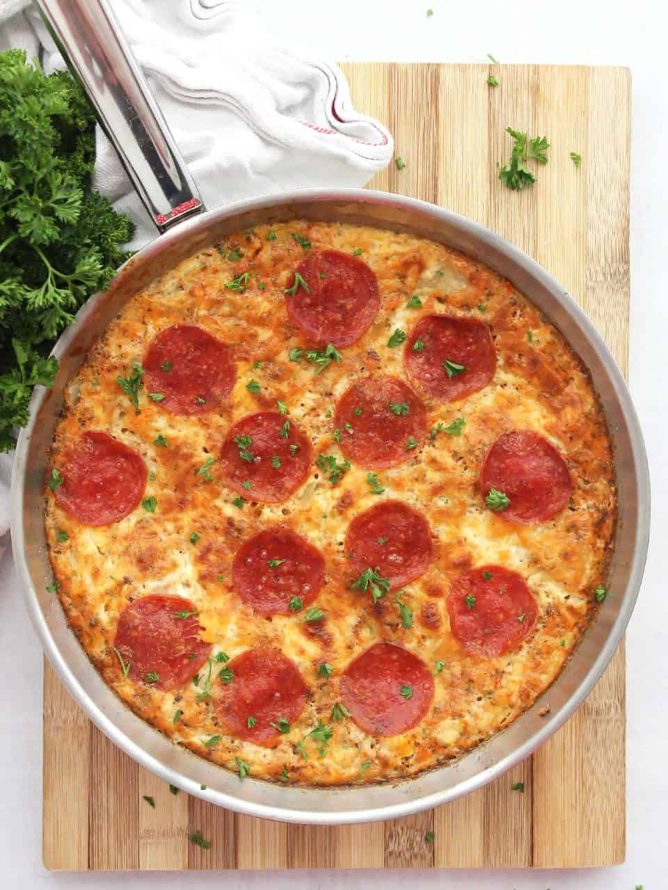 Overhead shot of a pepperoni pizza frittata in a silver skillet.