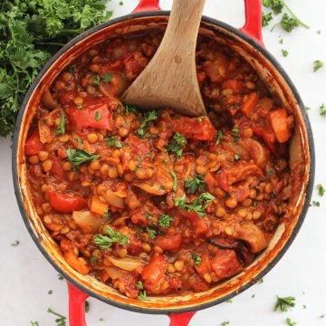 Roasted vegetable lentil bolognese in a red Dutch oven with a wooden spoon.