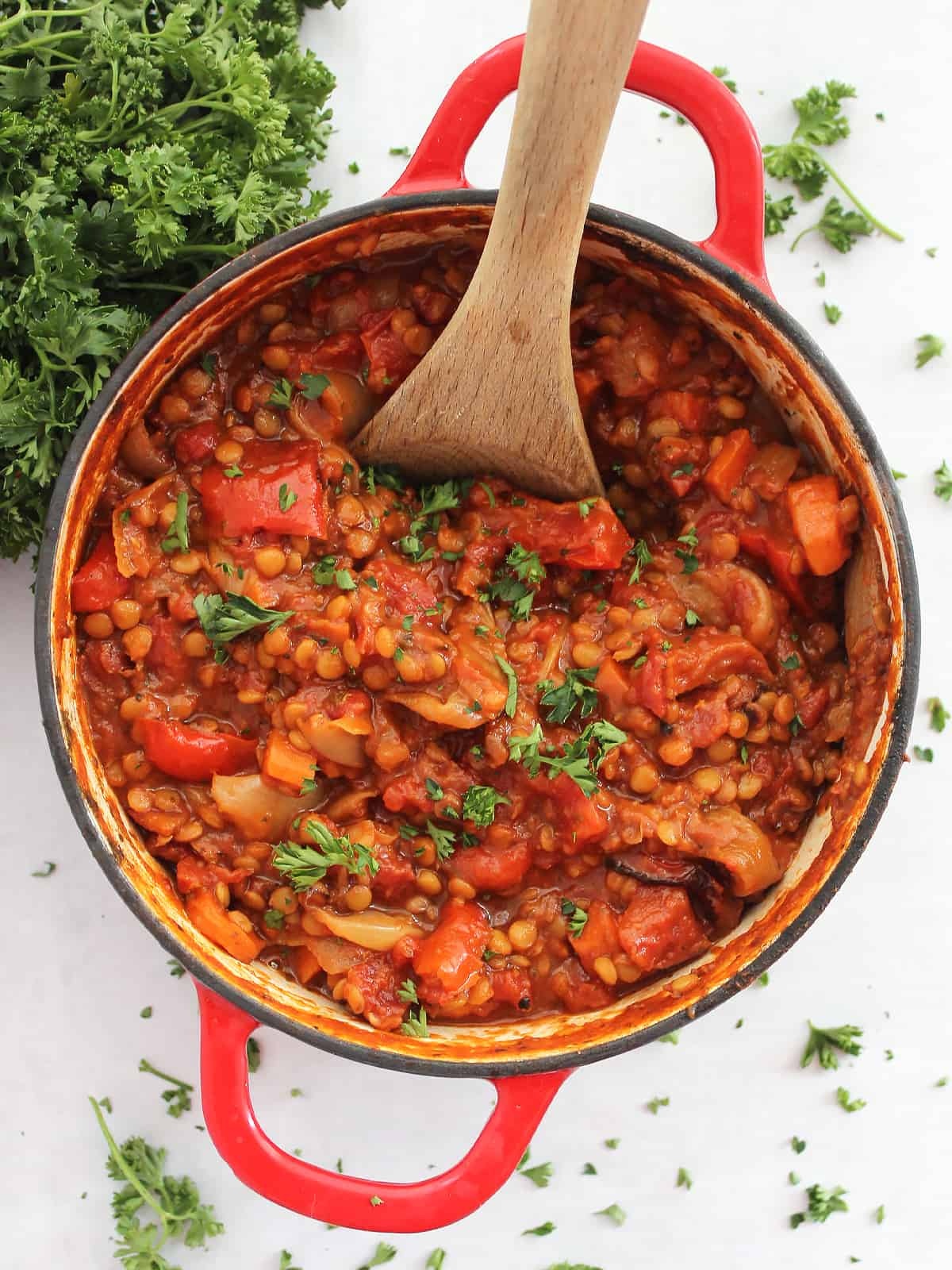 Overhead shot of roasted vegetable lentil bolognese in a Dutch oven garnished with fresh parsley.