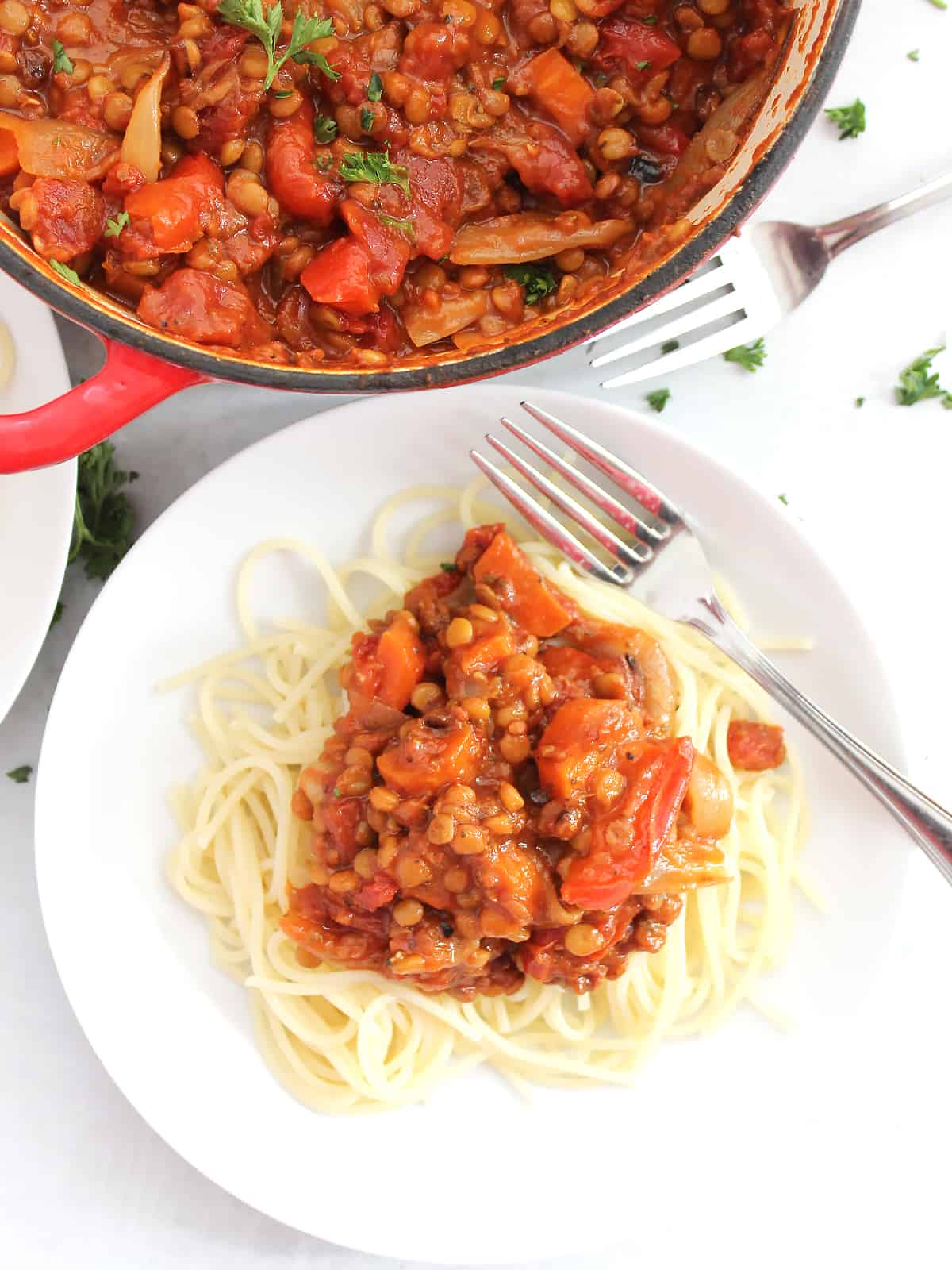 Overhead shot of the bolognese served on spaghetti with a fork on a plate.