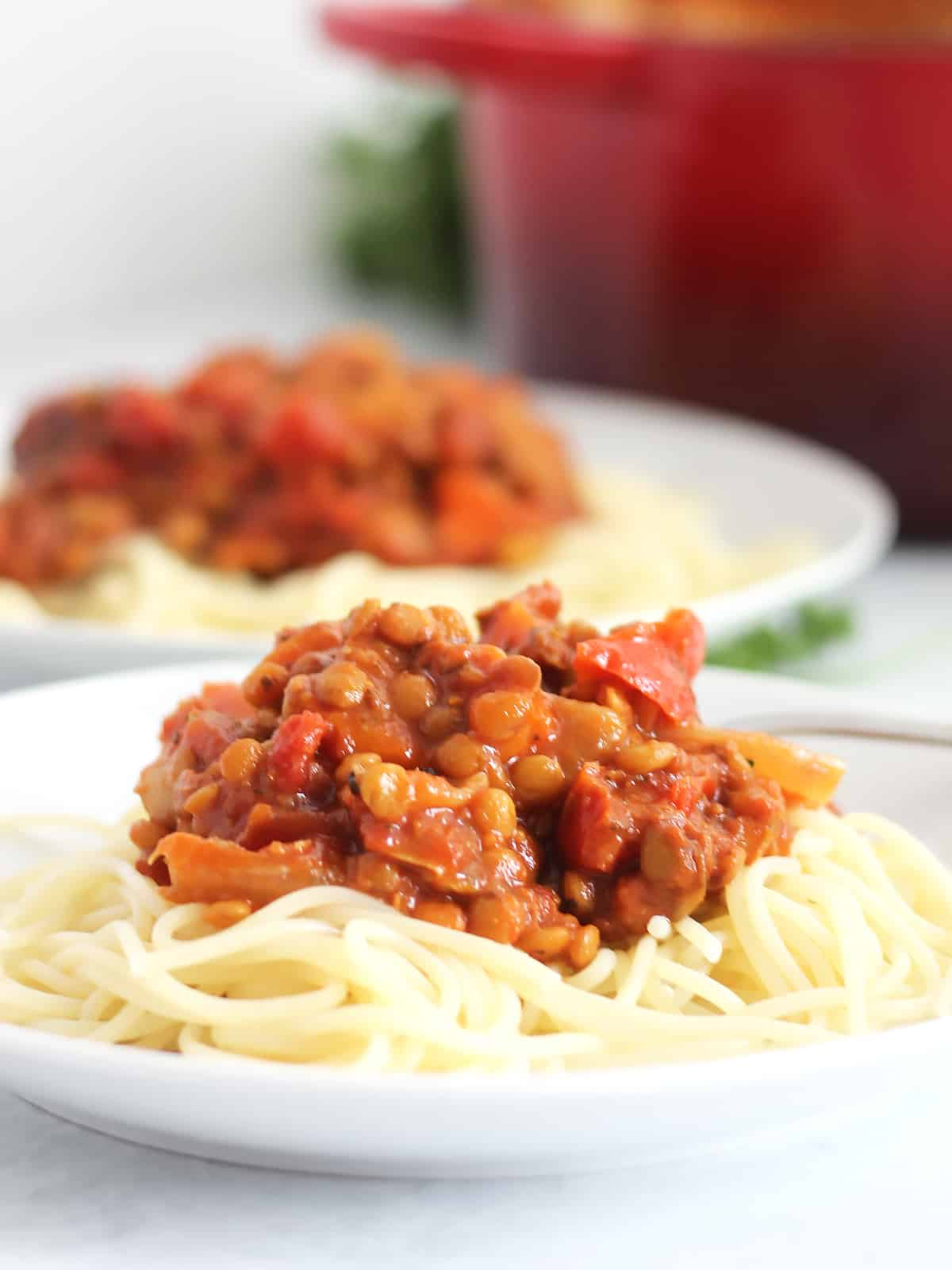Close up of the roasted vegetable lentil bolgnese on top of some spaghetti on a white plate.