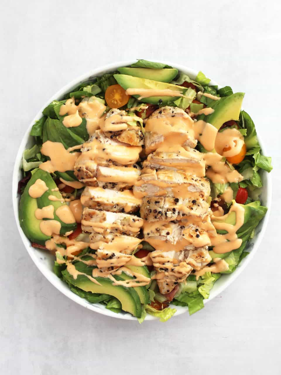 Overehead shot of a salad with chicken and avocado drizzled with a thick dressing.