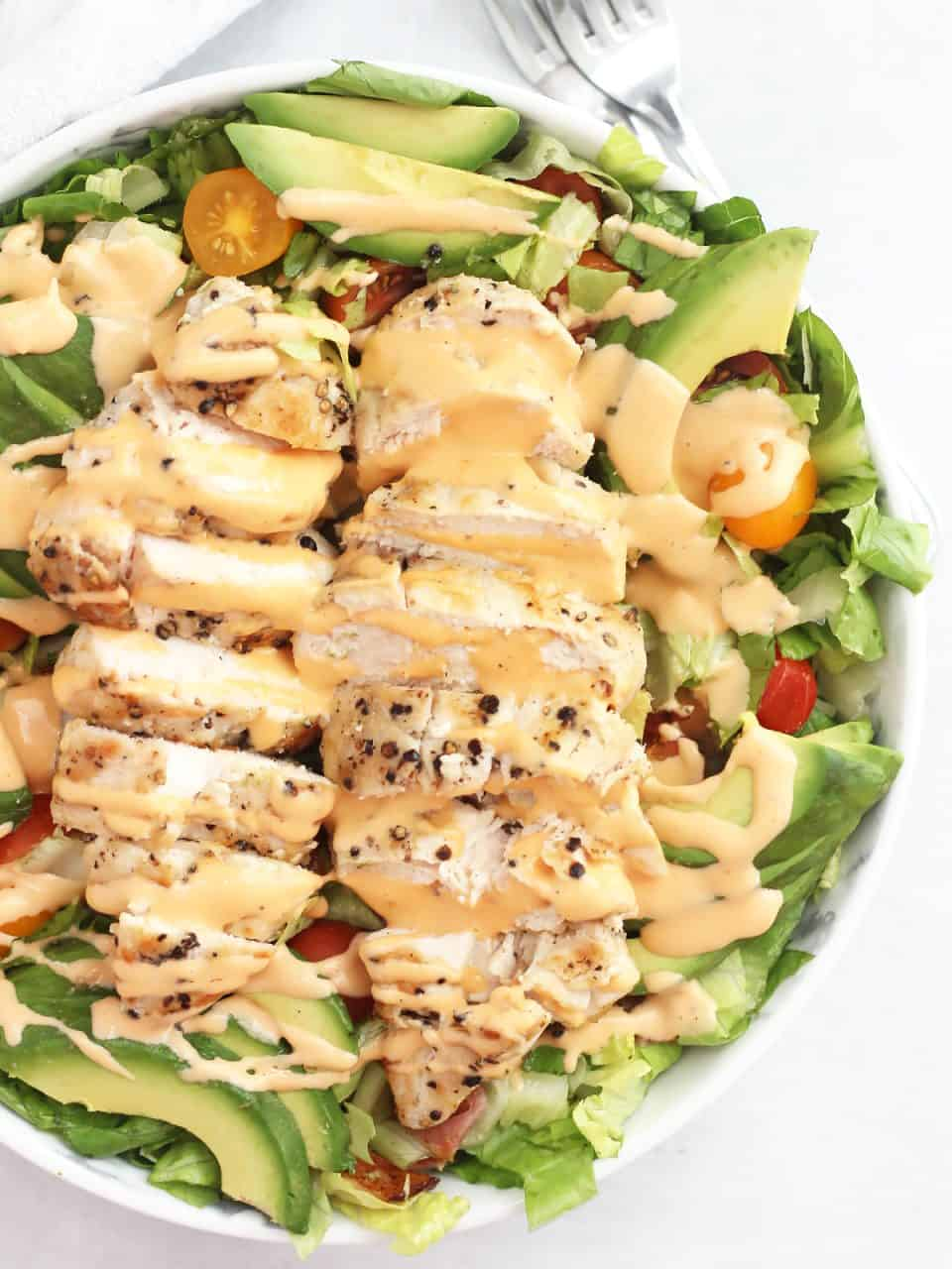 Overhead shot of two sliced chicken breasts on a bed of salad.