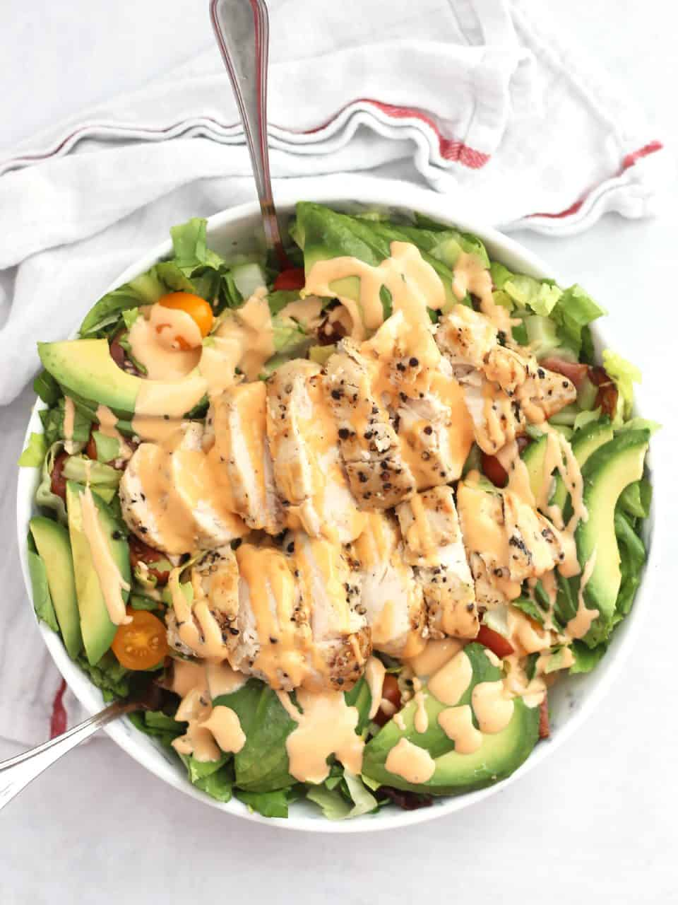 Overhead shot of a BLT chicken avocado salad in a bowl drizzled with a sauce.