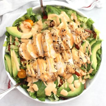 A BLT chicken avocado salad drizzled with a creamy dressing.