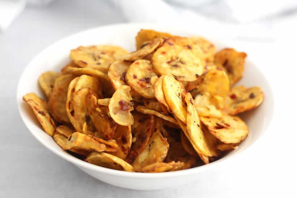 Close up of plantain chips served in a white bowl.