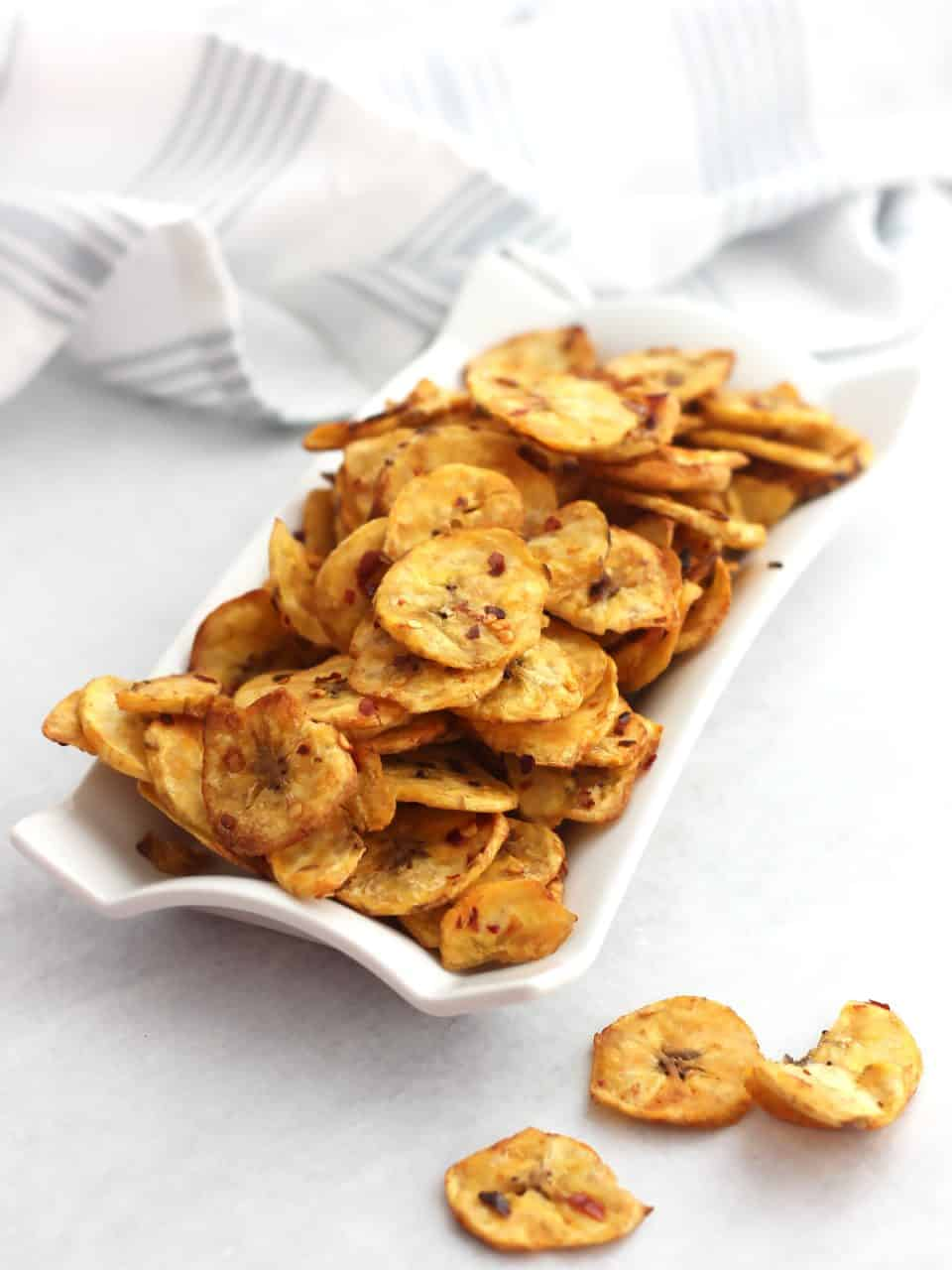 Air fryer plantain chips on a white serving dish next to a blue and white striped cloth.