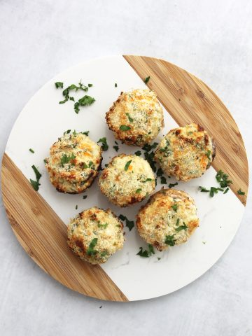Overhead shot of six air fryer stuffed mushrooms on a circular chopping board and garnished with parsley.