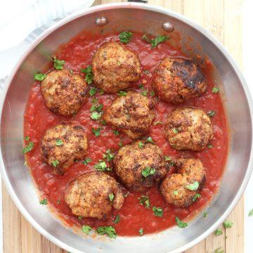 Air fryer turkey meatballs in a skillet with marinara sauce.