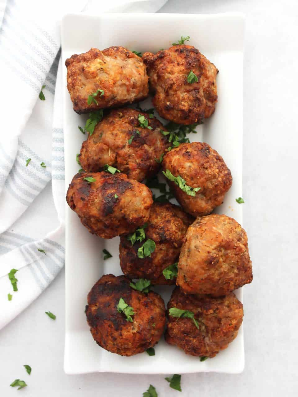 Overhead shot of air fryer turkey meatballs on a plate garnished with fresh parsley.