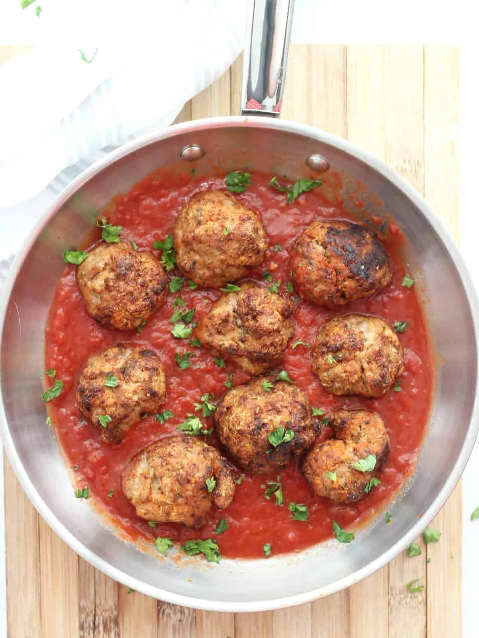 Air fryer turkey meatballs in a skillet with tomato sauce.