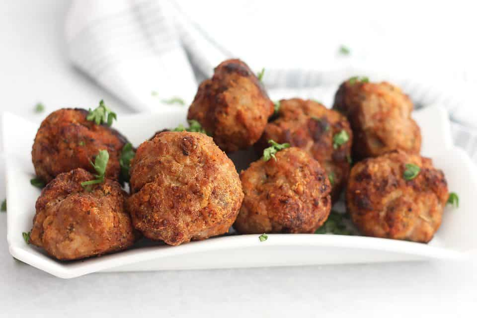 Air fried turkey meatballs on a white serving plate garnished with fresh parsley.