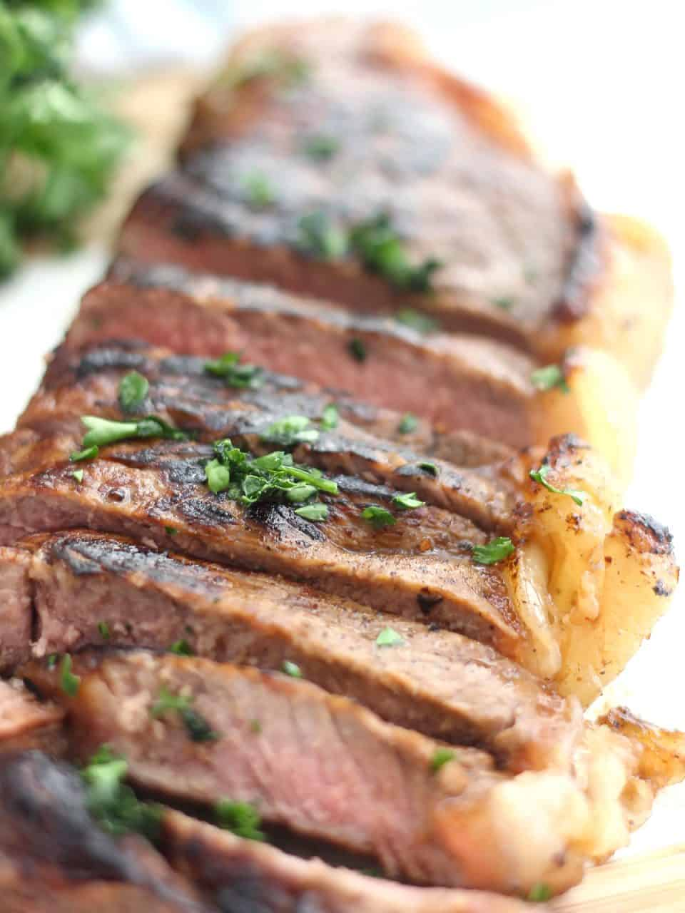 Close up of a sliced marinated steak garnished with parsley.
