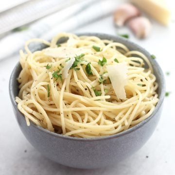 Garlic spaghetti in a blue bowl topped with shaved parmesan.