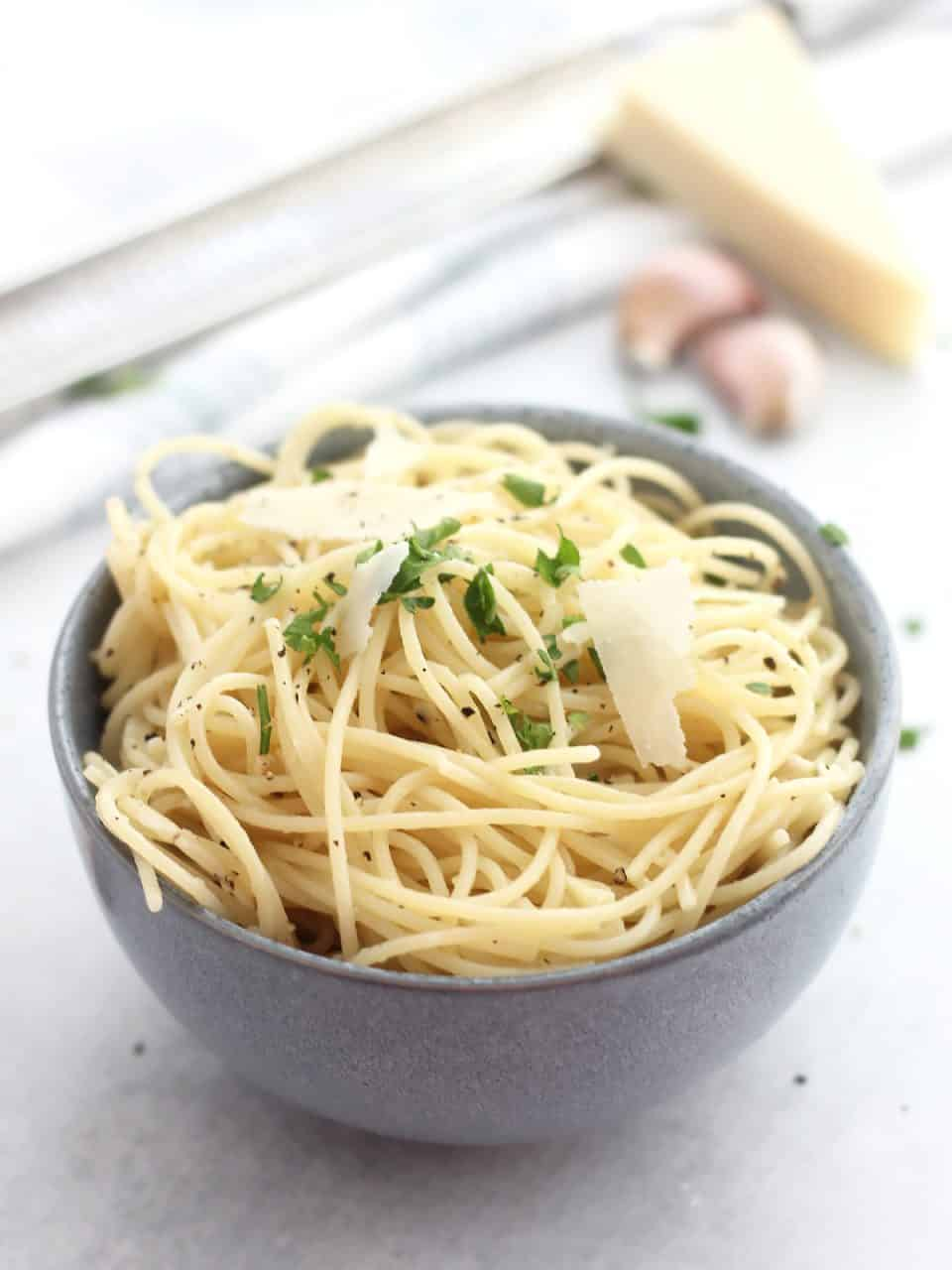 Garlic parmesan spaghetti in a blue bowl.