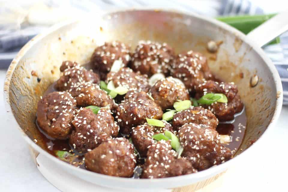 The cooked meatballs in a honey sriracha sauce in a silver skillet.