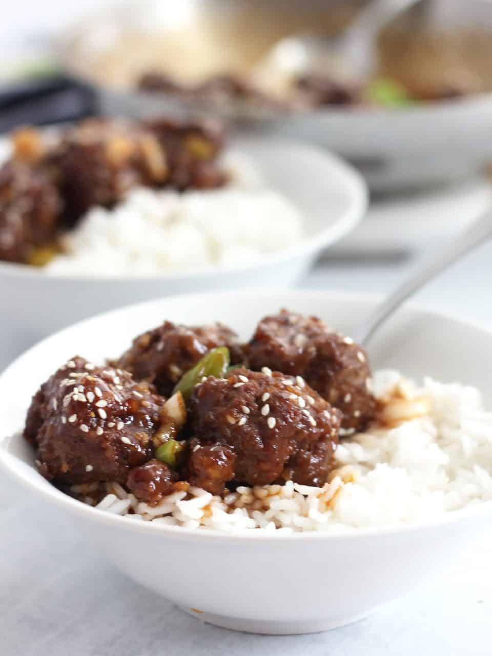 Four meatballs served in a bowl on a bed of rice.
