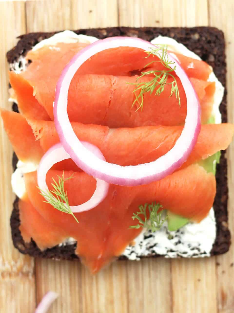 Overhead shot of a slice of bread topped with salmon and red onion.