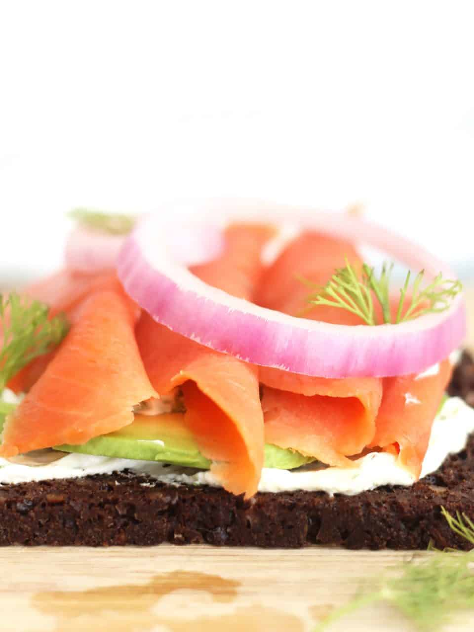 Close up from the side of a slice of rye bread topped with cream cheese, avocado, smoked salmon, red onion and fresh dill.
