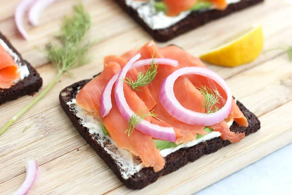 An open faced smoked salmon sandwich topped with red onion and fresh dill.